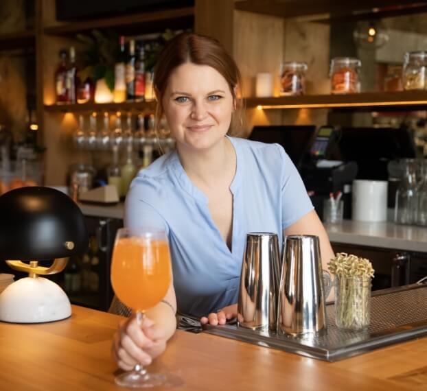 smiling bartender serving drink